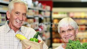 Senior couple with bag of veg in grocery store