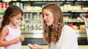 Mother and daughter picking out pepper in supermarket