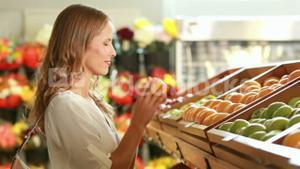 Woman picking out fruit in supermarket