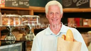 Senior man with baguettes in supermarket