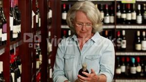 Senior woman picking a wine in off licence