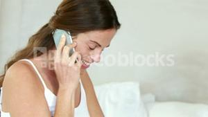 Pregnant woman relaxing on bed talking on phone