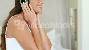 Pregnant woman relaxing on bed listening to music