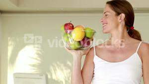 Pregnant woman holding fruit bowl