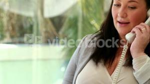 Pregnant businesswoman answering the phone