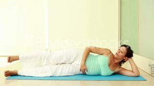 Pregnant woman exercising on exercise mat