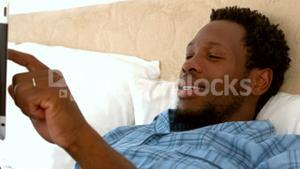 Man relaxing in his bed using tablet pc
