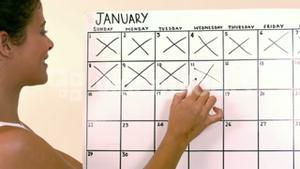 Woman marking off dates on calendar