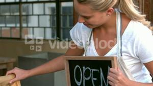 Cafe owner showing open sign