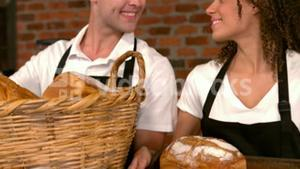 Cafe workers showing baskets of bread
