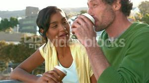 Happy business couple drinking a take-away coffee