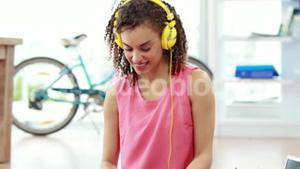 Casual businesswoman listening to music