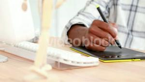 Serious businessman drawing on graphic tablet