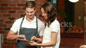 Smiling waiter using tablet with a customer
