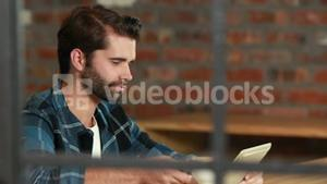 Smiling hipster man using a tablet and sipping coffee