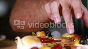 Close up hands tidying the pastries
