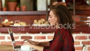 Smiling hipster woman working on laptop