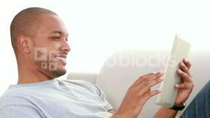 Relaxed man scrolling on the tablet