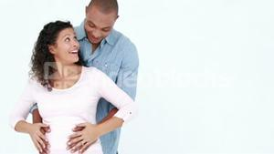 Pregnant woman and husband with arms around