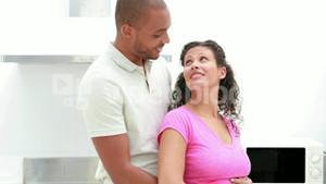Portrait of a pregnant couple with arms around