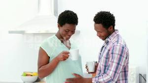 Pregnant couple drinking coffee in the kitchen