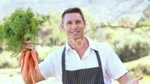 Smiling farmer handing a bunch of carrots