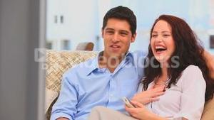 Couple laughting in front of the tv