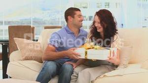 Man offering a present to his pregnant wife