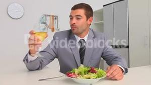 Businessman eating vegetables and drinking wine