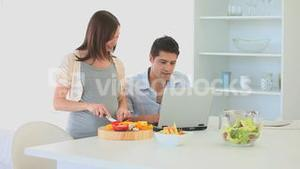 Pregnant woman cooking while her husband working on his laptop