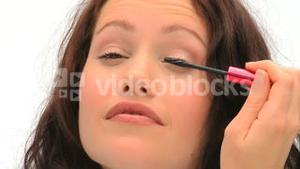 Brownhaired woman putting make-up