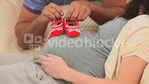 Future parents holding little red shoes