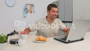 Casual man with a laptop taking his breakfast