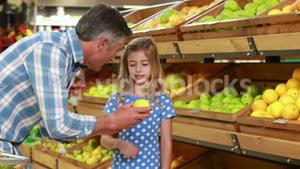 Smiling father showing lemon to daughter