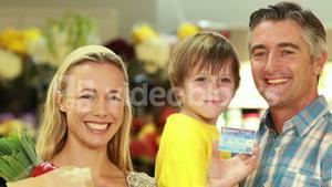 Smiling family with paper bag showing credit card