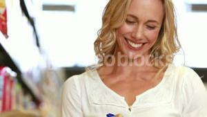 Smiling mother checking grocery list