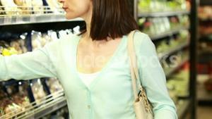 Smiling brunette shopping with grocery list