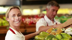 Smiling workers stocking vegetables