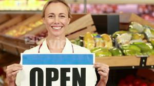 Smiling worker holding open sign