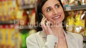 Smiling brunette phoning while shopping