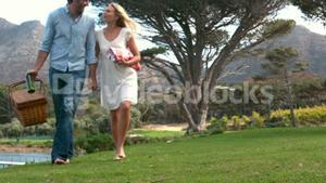 Happy couple walking with picnic basket in slow motion