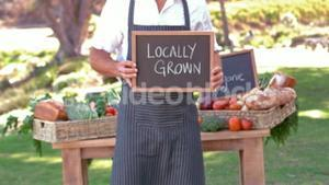 Smiling farmer holding locally grown sign in slow motion