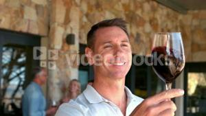 Smiling man examining red wine in slow motion