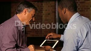 Colleagues using tablet at bar