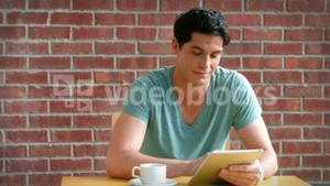 Handsome college student working on his digital tablet