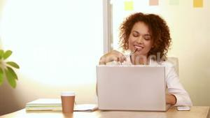 Smiling casual businesswoman using laptop