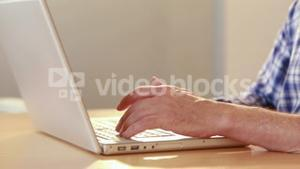Close up view of angry casual businessman using laptop