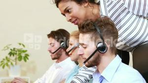 Smiling businesswoman helping call center agent