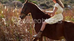 Pretty woman riding on a horse