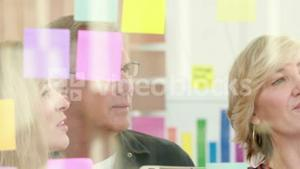 Businessman writing on post it with his colleagues